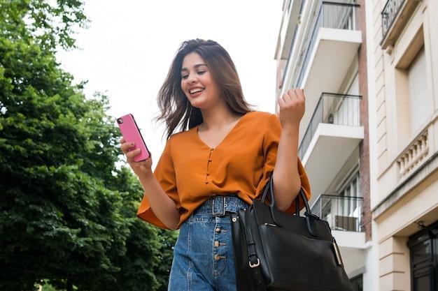 通りを屋外で歩いているときに彼女の携帯電話を使用して若い女性の肖像画。都市とコミュニケーションの概念。
