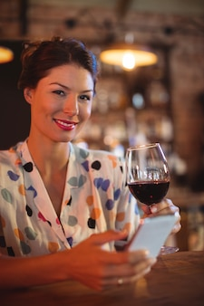 Портрет молодой женщины с помощью мобильного телефона с вином