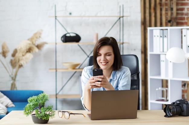 Портрет молодой женщины с помощью смартфона и улыбается