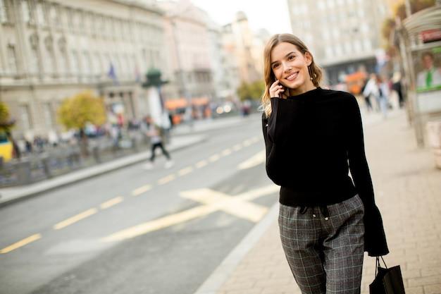 Портрет молодой женщины, ожидающей такси или автобуса на улице в городе