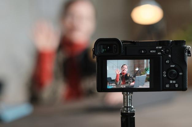 노트북으로 테이블에 앉아 카메라에 자신을 기록하는 동안 카메라를 흔드는 젊은 여성의 초상화