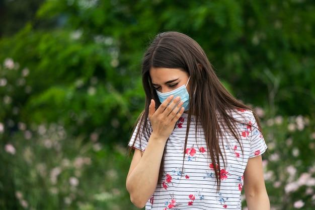 Портрет молодой женщины в защитной маске чихает на зеленом фоне природы с цветами в защитной медицинской маске, пандемии коронавируса