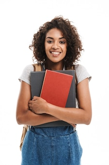 Портрет молодой женщины в рюкзаке, улыбаясь и держа тетради, изолированные на белой стене