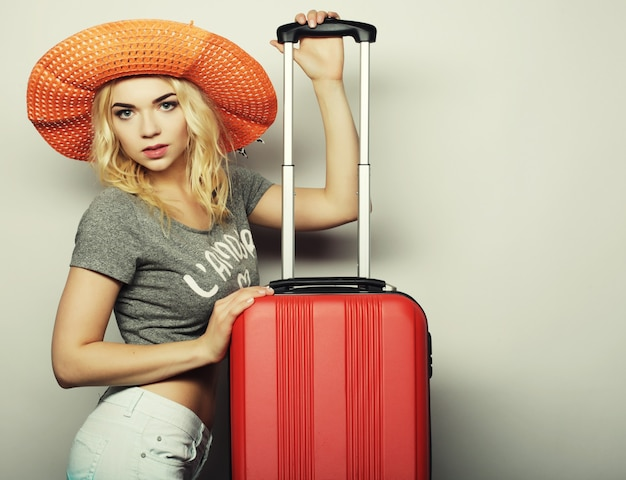 Портрет молодой женщины в большой соломенной оранжевой шляпе, стоящей с оранжевой дорожной сумкой