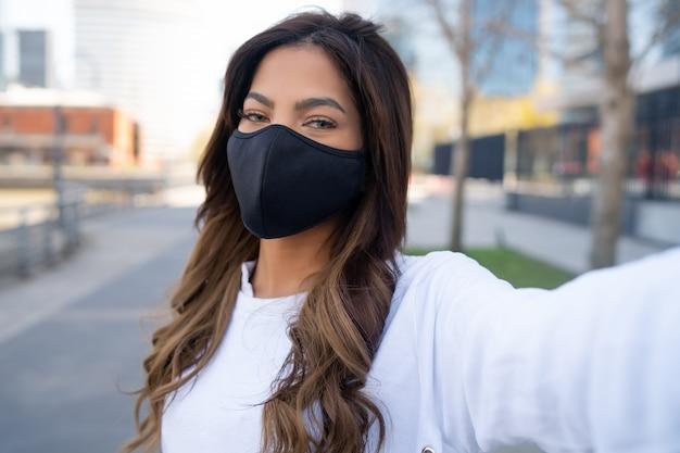 Портрет молодой женщины в маске для лица и принимая селфи, стоя на открытом воздухе на улице. городская концепция. новая концепция нормального образа жизни.