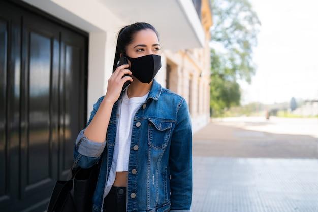 路上で屋外に立っている間、フェイスマスクを着用し、電話で話している若い女性の肖像画。アーバンコンセプト。新しい通常のライフスタイルのコンセプト。