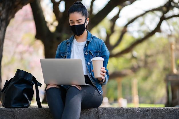 フェイスマスクを着用し、屋外に座ってラップトップを使用して若い女性の肖像画。アーバンコンセプト。
