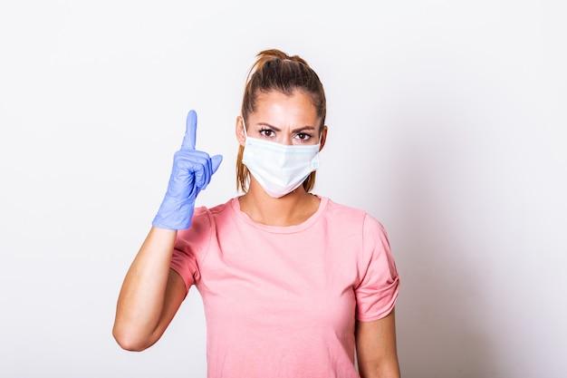 彼女の指で現れるフェイスマスクを着た若い女性の肖像画。 covid-19防止コンセプト