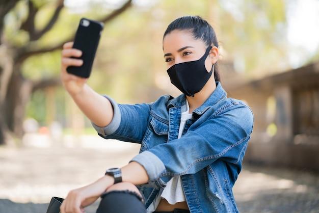 Facee 마스크를 착용하고 야외에서 그녀의 mophile 전화로 셀카를 복용하는 젊은 여자의 초상화