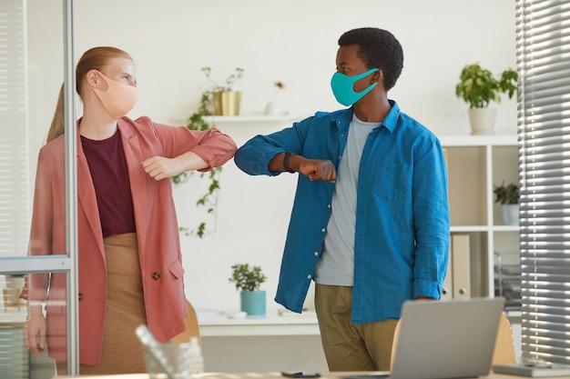 포스트 유행성 사무실에서 일하는 동안 비접촉식 인사로 아프리카 계 미국인 동료와 팔꿈치를 부딪 치는 마스크를 착용하는 젊은 여자의 초상화