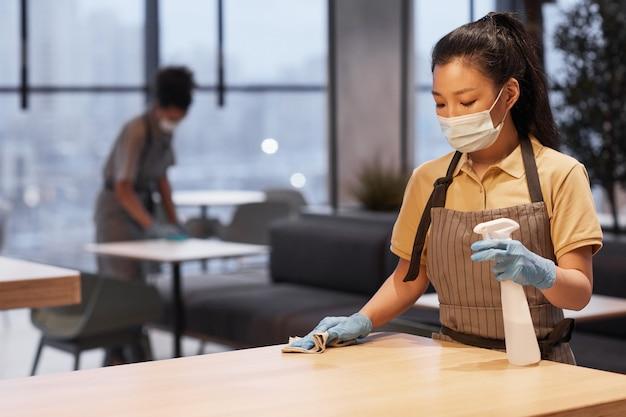 モダンなレストランのインテリア、covid安全コンセプト、コピースペースでテーブルを掃除しながらマスクを身に着けている若い女性の肖像画