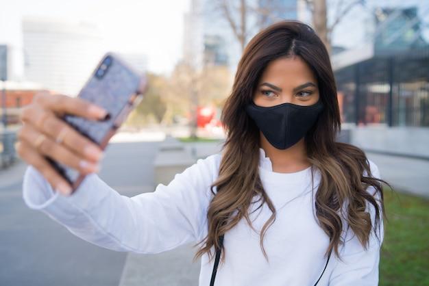 保護マスクを着用し、屋外に立っている間彼女のmophile電話でselfiesを取る若い女性の肖像画。