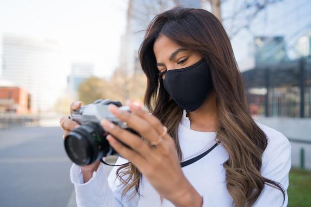 Портрет молодой женщины в защитной маске и с помощью камеры во время фотографирования в городе. новая концепция нормального образа жизни.