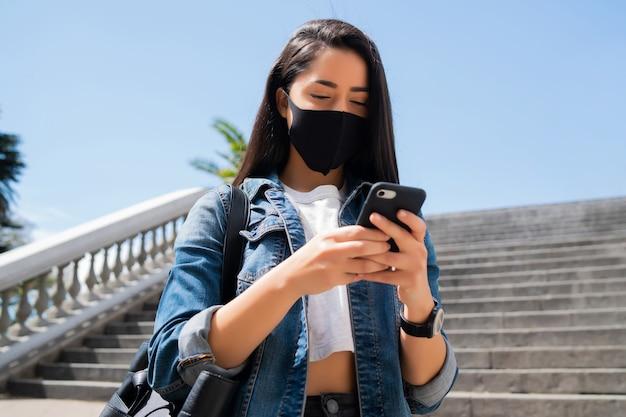 保護マスクを着用し、路上で屋外に立っている間彼女の携帯電話を使用して若い女性の肖像画。