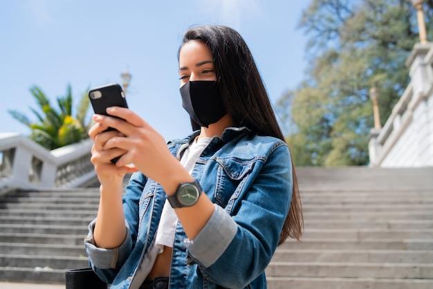 보호 마스크를 착용하고 거리에 야외에서 서있는 동안 그녀의 휴대 전화를 사용하는 젊은 여자의 초상화.