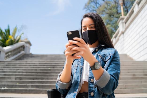 保護マスクを着用し、路上で屋外に立っている間彼女の携帯電話を使用して若い女性の肖像画