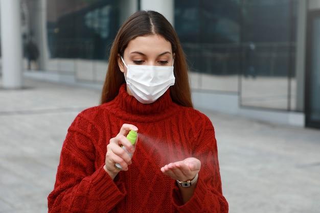 彼女の手にアルコール消毒剤をスプレーする保護医療マスクを身に着けている若い女性の肖像画