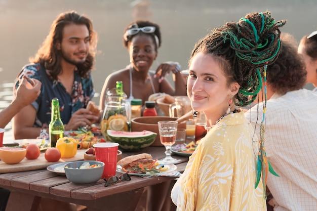 야외에서 그녀의 친구와 함께 테이블에서 저녁 식사를하는 동안 젊은 여자의 초상화