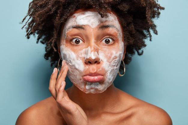 彼女の肌を洗うアフロの散髪を持つ若い女性の肖像画