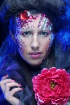 大きな赤い花を保持している芸術的な顔を持つ若い女性の肖像画