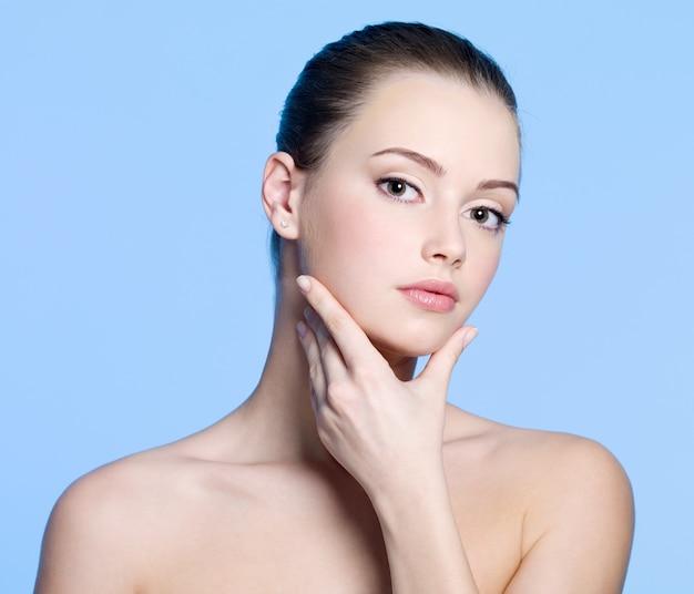 Портрет молодой женщины с красивой чистой свежей кожей на лице - синий фон