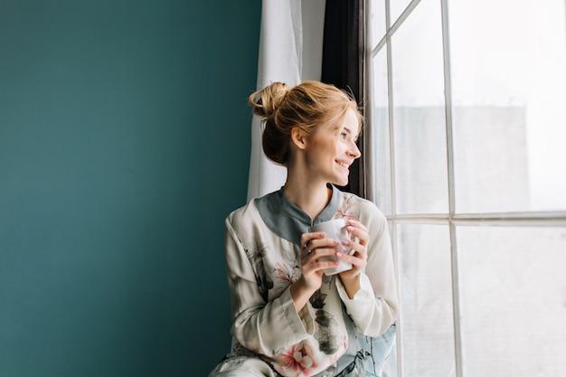 大きな窓の横にあるコーヒーやお茶を飲んで、笑って、自宅で幸せな朝を楽しんでいるブロンドの髪を持つ若い女性の肖像画。ターコイズブルーの壁。花にシルクのパジャマを着ています。