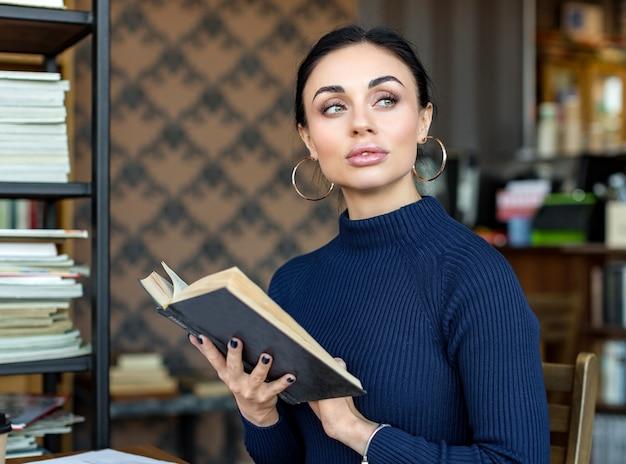 Портрет молодой женщины с книгой в библиотеке.