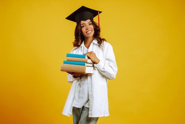 Портрет молодой женщины с книгами, позирующими на желтом.