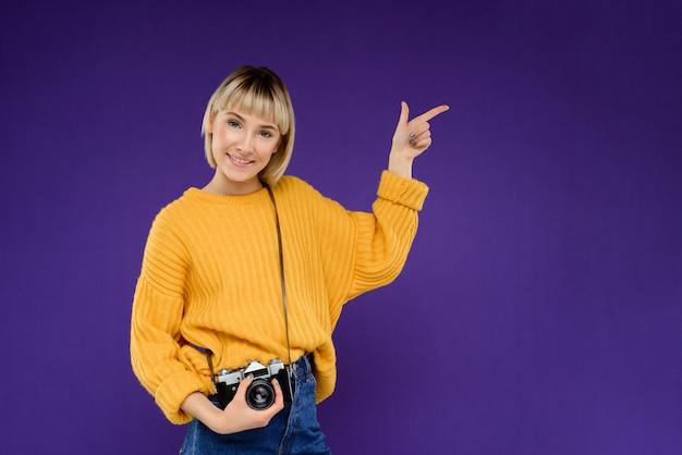 Портрет молодой женщины с камерой над фиолетовой стеной