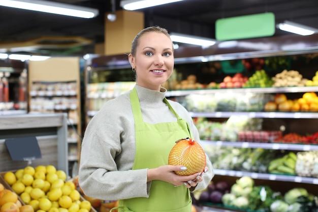 가 게에서 감귤 류의 과일을 가진 젊은 여자의 초상화. 중소기업 소유자