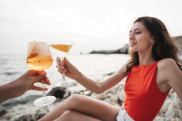 해변에서 칵테일 잔을 들고 있는 젊은 여성의 초상화