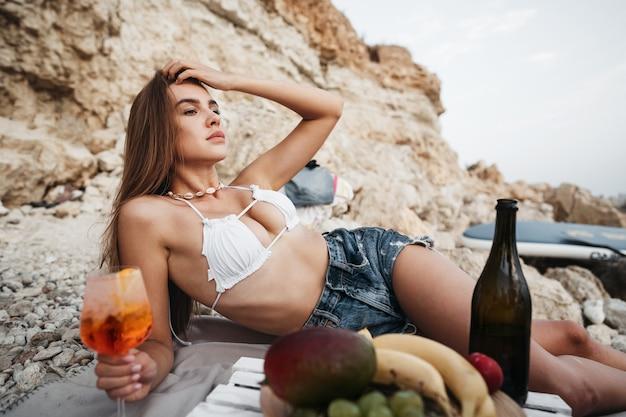 Портрет молодой женщины с коктейлем на пляже