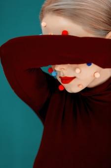 얼굴에 색된 공을 가진 젊은 여자의 초상화