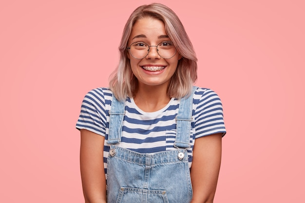 オーバーオールを着て色の髪を持つ若い女性の肖像画