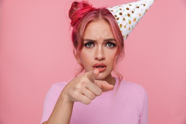 あなたに指を指すパーティーコーンを身に着けているカラフルな髪型を持つ若い女性の肖像画