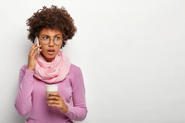선명한 검은 머리를 가진 젊은 여성의 초상화, 귀 근처에 휴대 전화를 들고, 테이크 아웃 커피를 마시고, 불쾌한 것을 논의하고, 목에 스카프를 착용하고, 옆으로 보이며, 실내 포즈를 취합니다.