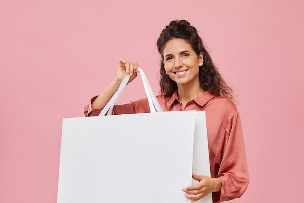 大きな買い物袋を保持し、ピンクの背景にカメラで笑って巻き毛の若い女性の肖像画