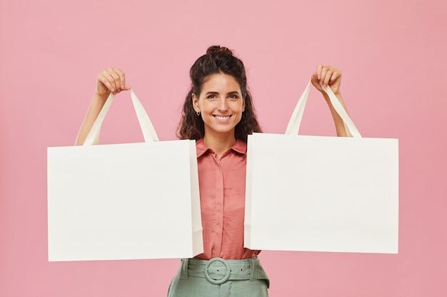 Портрет молодой женщины с вьющимися волосами, держащей хозяйственные сумки и улыбающейся изолированной на розовом фоне