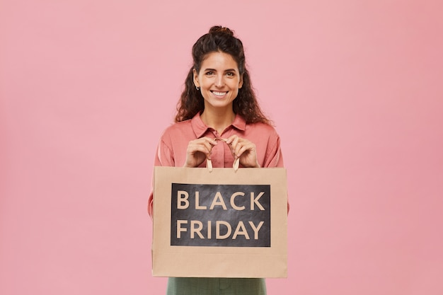 Портрет молодой женщины с вьющимися волосами, улыбающейся, держащей покупку из черной пятницы на розовом фоне
