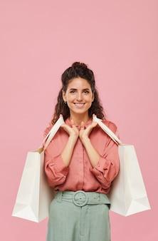 Портрет молодой женщины с вьющимися волосами, улыбаясь, держа покупки на розовом фоне
