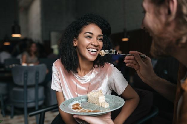 레스토랑에서 케이크를 먹고 검은 곱슬 머리를 가진 젊은 여자의 초상화