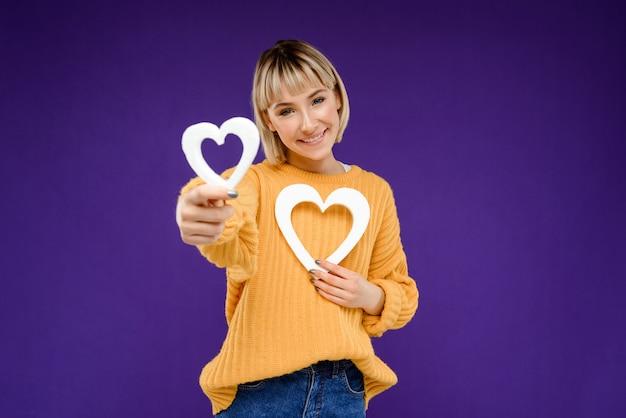 Портрет молодой женщины с сердцем декора над фиолетовой стеной