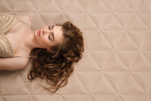 カーペットの上に横たわっているドレスと若い女性の肖像画