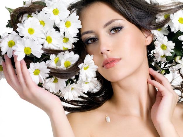 그녀의 긴 머리에 꽃을 가진 젊은 여자의 초상화-가로