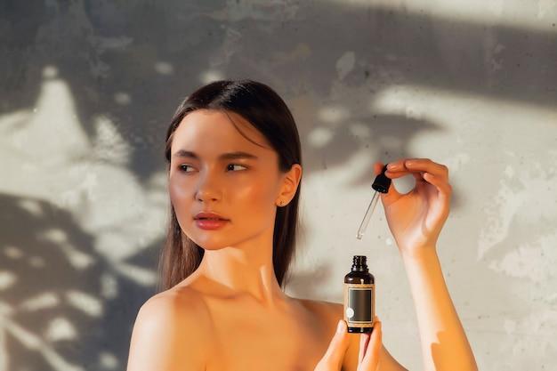 葉から日陰で古い壁の背景でポーズをとって新鮮な完璧な肌を持つ若い女性の肖像画。美容と治療の概念。健康的なライフスタイル、spa、セルフケアの広告コンセプト