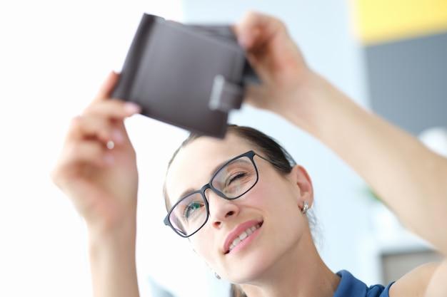 眼鏡をかけた若い女性の肖像画は、空の財布のクローズアップを調べます