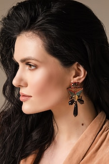 健康な肌と壁に隔離された彼女の耳にイヤリングを持つ若い女性の肖像画