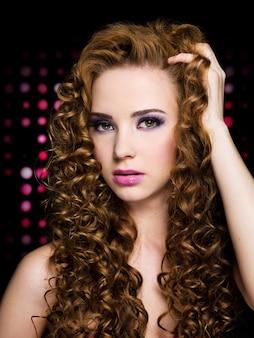 Портрет молодой женщины с длинными вьющимися волосами.