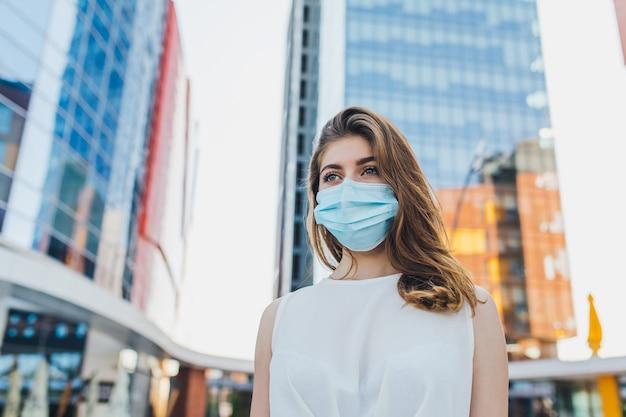 Портрет молодой женщины с маской для защиты от вспышки коронавируса в городе