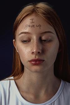 精神障害を持つ若い女性の肖像画。あきらめた言葉で額に刺青を入れた画像。
